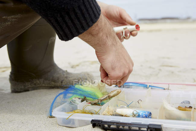 Cropped shot of male hand preparing fishing hook on beach — Stock Photo