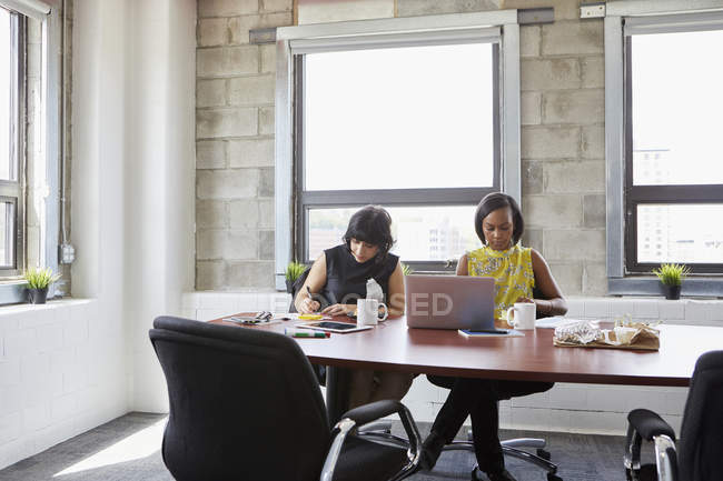 Two women in meeting room using laptop and writing in notebook — Stock Photo