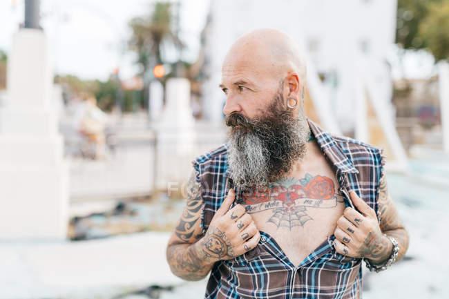 Hipster mâle mature, révélant la poitrine tatouée — Photo de stock