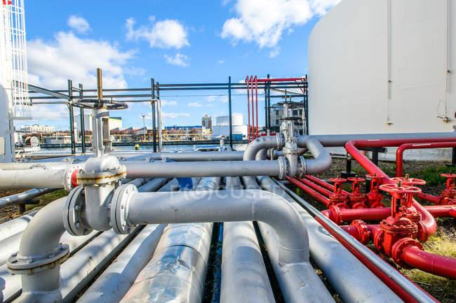 Серебряные и красные промышленные трубопроводы и клапаны на биотопливе — стоковое фото
