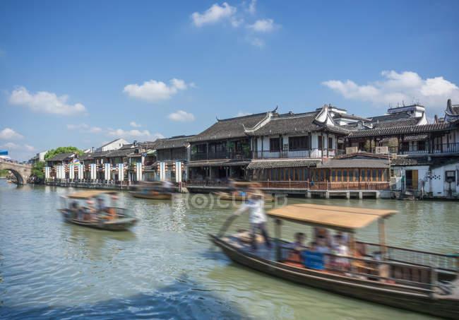 Flussschiffe auf Wasserstraße mit traditionellen Uferpromenade Gebäuden, Shanghai, China — Stockfoto