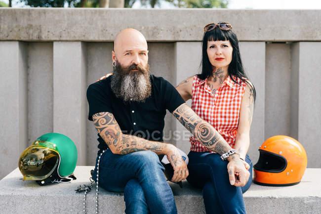 Tätowiert Hipster paar sitzt an Wand, Porträt — Stockfoto