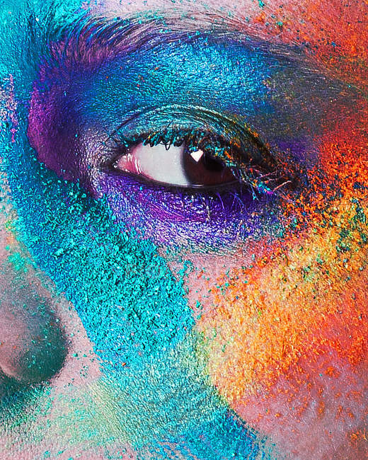 Young woman face with multi colored powder eye shadow — Stock Photo