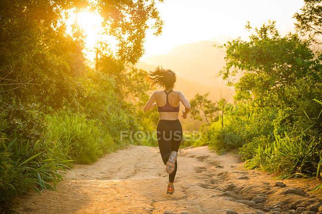 Rückansicht einer Frau, die auf Feldweg läuft — Stockfoto