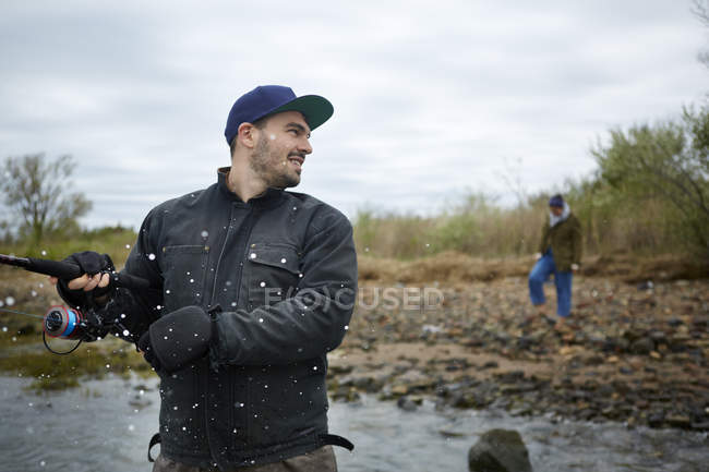 Young man splashed by sea while fishing — Stock Photo
