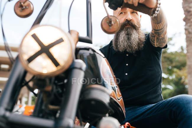 Niedrigen Winkel Blick auf ältere männliche Hipster rittlings auf Motorrad — Stockfoto