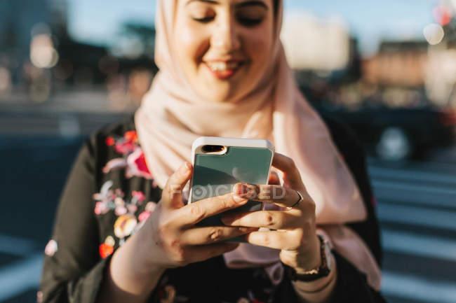 Молодая женщина в хиджабе смотрит на смартфон — стоковое фото