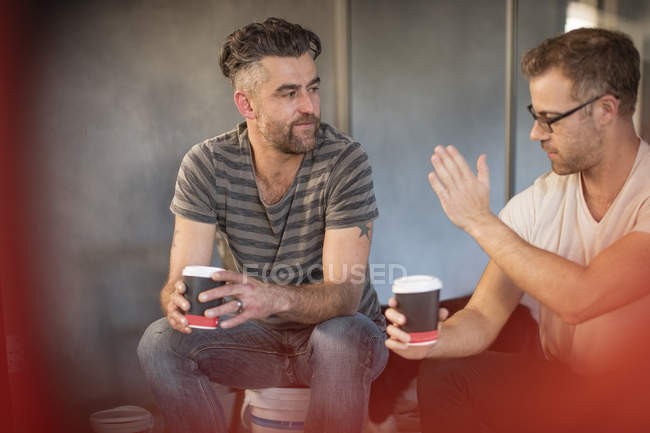 Two men taking break with coffee cups and having discussion — Stock Photo
