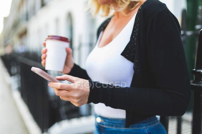 Donna con tazza di carta di caffè utilizzando smartphone — Foto stock