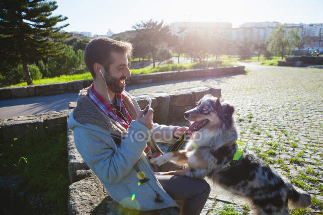 Man holding smartphone and playing with dog in city park — Stock Photo