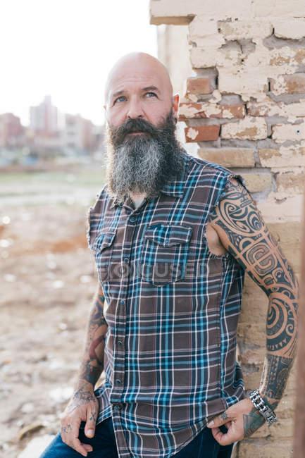 Татуированный взрослый хипстер, прислонившийся к стене разрушенного здания — стоковое фото