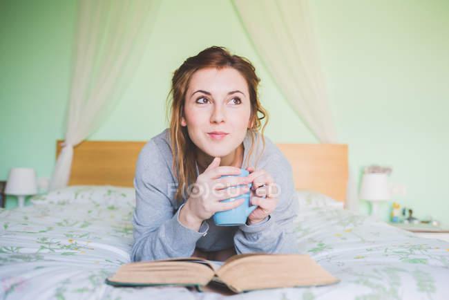 Молодая женщина лежит на кровати держа чашку кофе и глядя вверх — стоковое фото