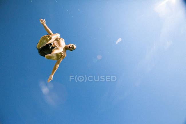 Vue à angle bas de Jeune homme sautant — Photo de stock