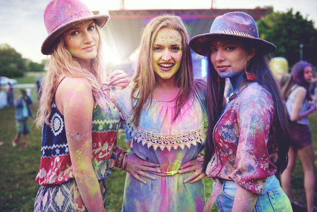 Portrait of three young women covered in colored chalk powder at festival — Stock Photo