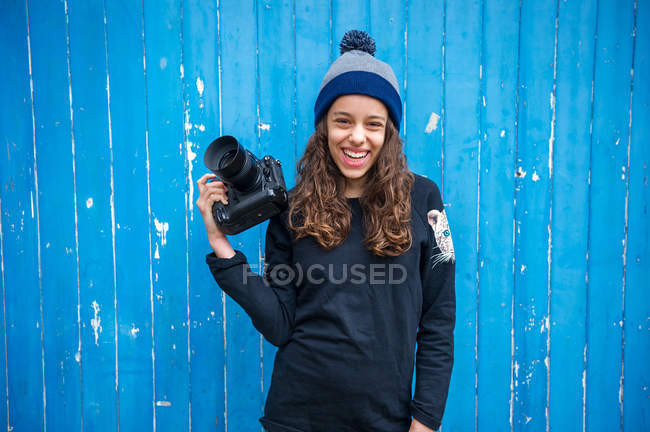 Девушка держит камеру на синем деревянном фоне — стоковое фото