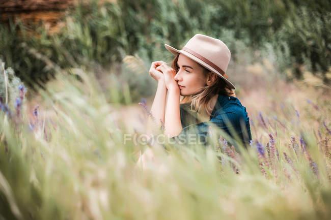 Donna in cappello seduta in erba lunga — Foto stock