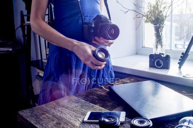 Woman holding camera and camera lens — Stock Photo