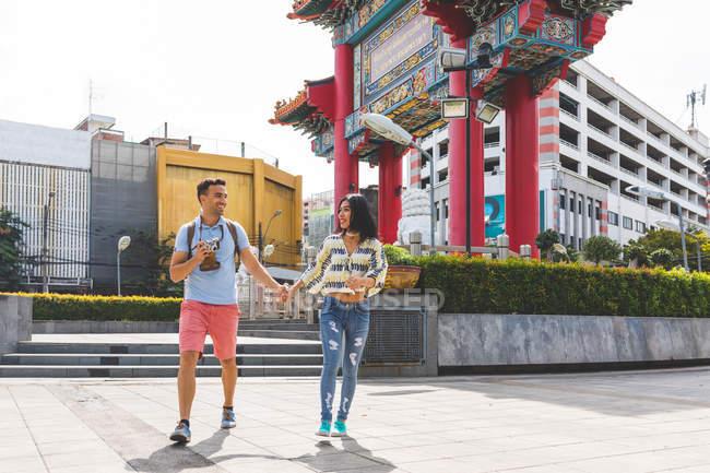 Молодая пара туристов, идущих по тротуару, Бангкок, Таиланд — стоковое фото