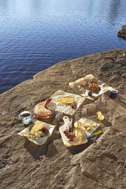 Selección de quesos, dispuestos en roca, junto al lago, Colgate Lake Wild Forest, Catskill Park, New York State, EE.UU. - foto de stock