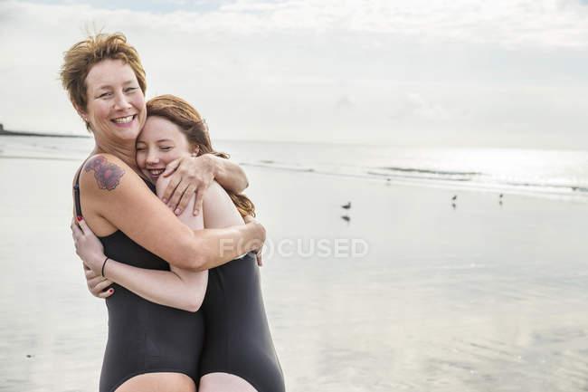 Мати і дочка сміятися і обіймати на пляжі — стокове фото