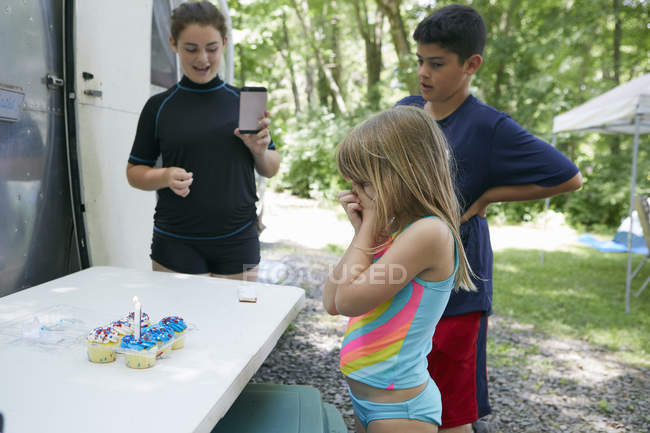 Three children standing near table with cakes — Stock Photo