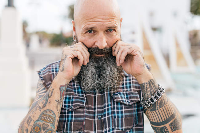 Portrait de hipster mâle mature, tirant sur sa moustache — Photo de stock