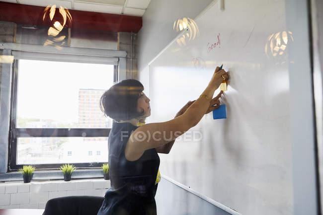 Deux femmes au bureau de coller des notes sur le tableau blanc — Photo de stock