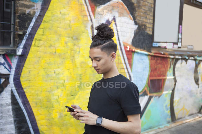 Side view of Young man using smartphone against wall with graffiti — Stock Photo