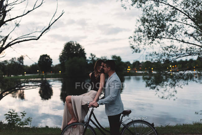 Романтическая молодая пара на велосипеде смотрит друг на друга у озера в сумерках — стоковое фото