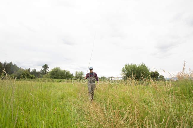 Fisherman with fishing rod walking on grass field, Clark Fork, Montana — Stock Photo