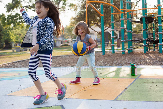 Two children playing on basketball in playground — Stock Photo