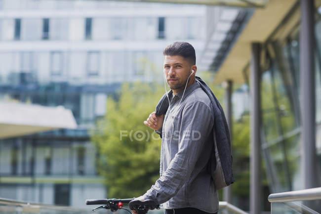 Человек с наушниками, перевозящих куртка через плечо — стоковое фото