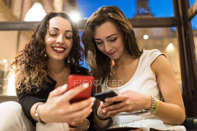 Молоді жінки, дивлячись на смартфонах разом — стокове фото