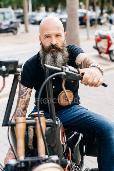 Retrato de hipster hombre maduro a horcajadas sobre la moto en el estacionamiento - foto de stock