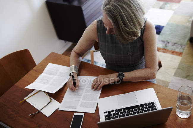 Senior businesswoman sitting at desk, laptop in front of her, signing document — Stock Photo