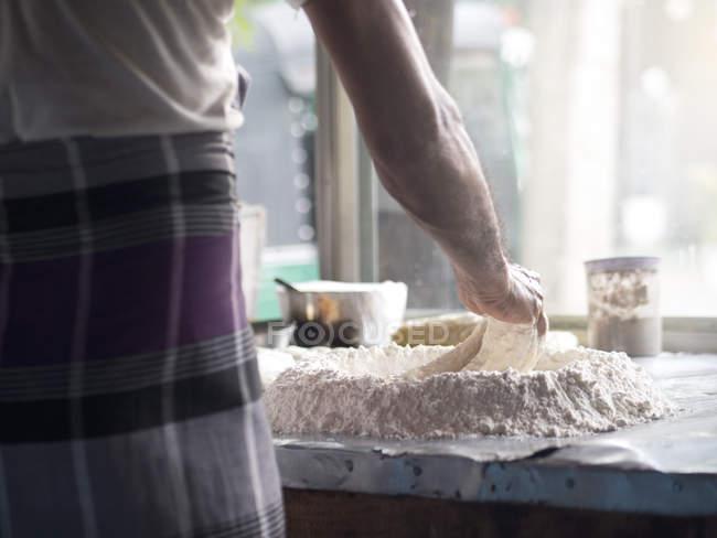 Vue arrière de l'homme prépare la pâte dans la cuisine — Photo de stock