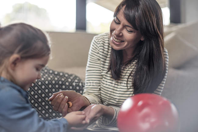 Mädchen, die Hand der Mutter für Sparschwein Münze auswählen — Stockfoto