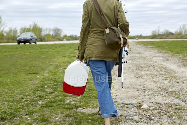 Jeune femme marchant avec canne à pêche et boîte à tache — Photo de stock