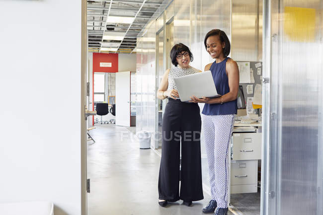 Two women standing in office corridor and looking at laptop — Stock Photo