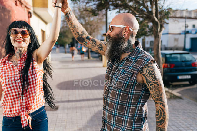 Mature hipster couple dancing on sidewalk — Stock Photo