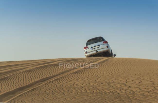 Fora o veículo de estrada dirigindo sobre a parte superior das dunas do deserto, Dubai, Emirados Árabes Unidos — Fotografia de Stock