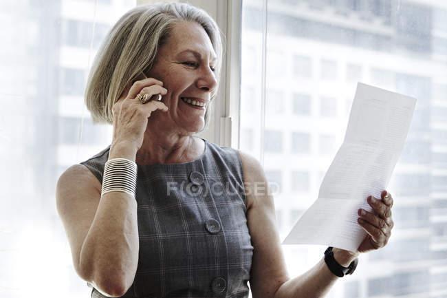 Старшого бізнес-леді виступаючи на смартфоні, дивлячись на документ — стокове фото