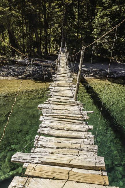 Río de cruce de puente peatonal de madera Azul, Cajon del Azul cerca de El Bolson, Patagonia, Argentina - foto de stock