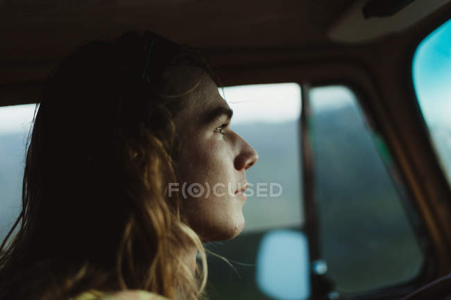 Head shot of long haired young man driving — Stock Photo