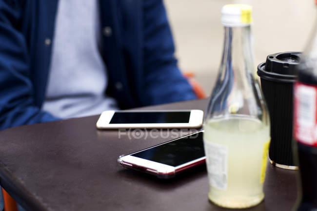 Immagine ritagliata di uomo seduto a tavola con due smartphone — Foto stock