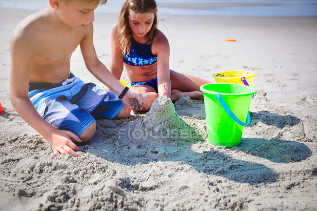 Двое детей, игры с песком на пляже — стоковое фото