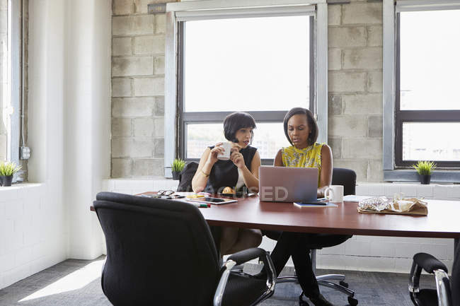 Two women using laptop at meeting room table — Stock Photo