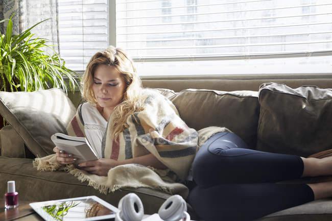 Молодая женщина читает книгу на диване — стоковое фото