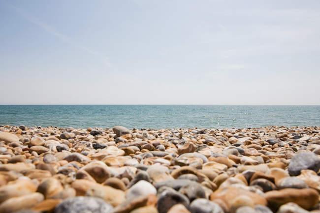 Spiaggia di ghiaia e paesaggio marino all'orizzonte, Inghilterra — Foto stock