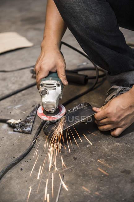 Close up of mechanic working at custom motorbike shop, Bangkok, Thailand — Stock Photo